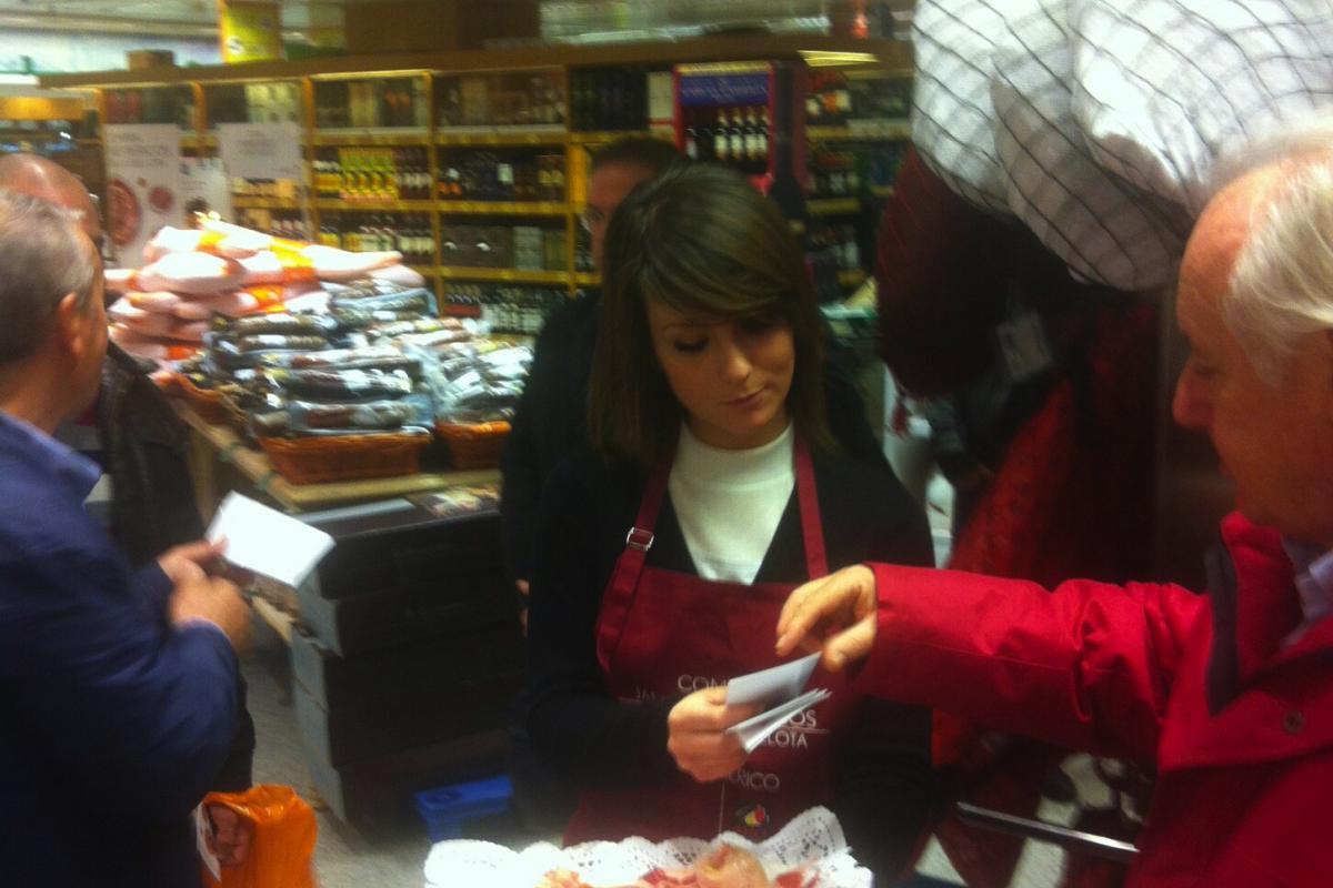 Nuestra azafata ofreciendo jamón y información a los clientes
